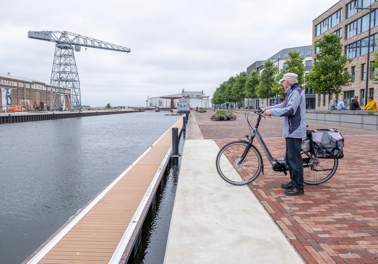 Een fietser bewondert het deel van de passantensteiger dat al langs de Peperdijk is te bewonderen. Voor het eind van de zomer, als aan de overkant langs de Machinefabriek ook afmeersteigers liggen, moeten de eerste jachten aan kunnen leggen.