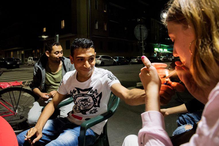 Ahmed met een vuurtje voor Jana in Milaan: 'Ik heb me hier altijd welkom gevoeld.'  Beeld Sanne De Wilde