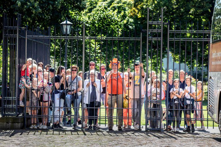 Bij Paleis Noordeinde proberen sportfans een blik op te vangen van de olympische sporters.  Beeld Foto Raymond Rutting / de Volkskrant
