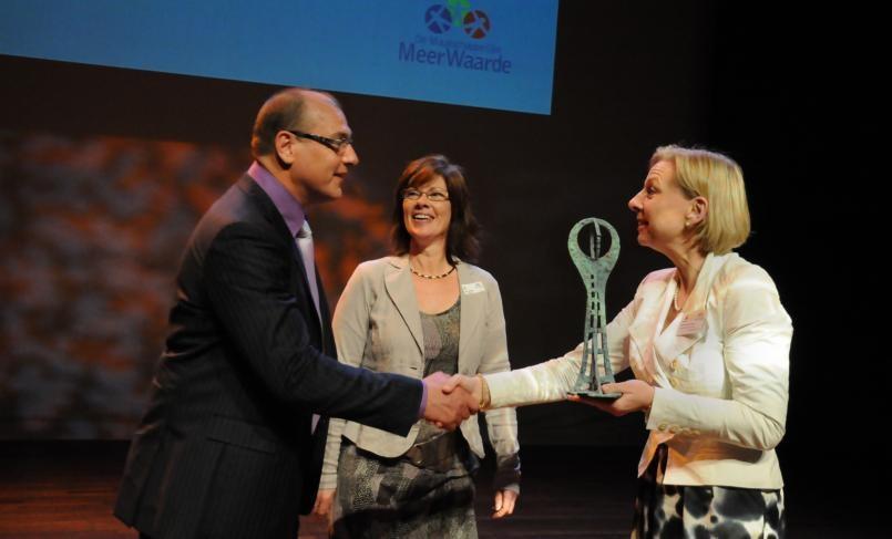 Ronnie Reijnen en zijn echtgenote nemen de prijs in ontvangst uit handen van Annemarie Scholtis van de Rabobank. foto Theo van Zwam