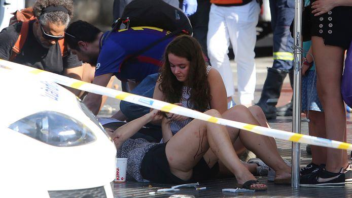 Voorbijgangers bieden de eerste hulp na de aanslag op de Ramblas.