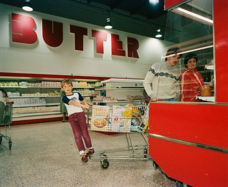 Een jongetje probeert zich te vermaken in een supermarkt, waar je blijkbaar ook boter kunt kopen. Beeld ©Martin Parr / Magnum Photos
