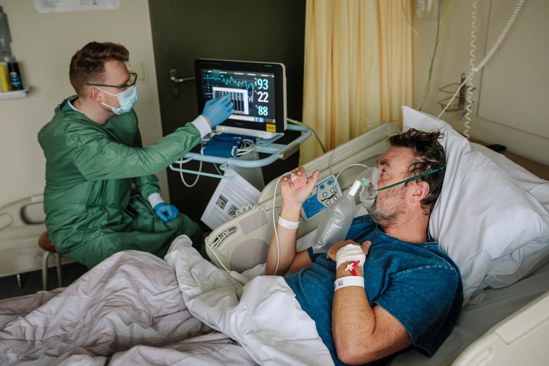 Verpleegkundige Nick Luchtmeijer let op de hartslag en ademfrequentie van coronapatiënt Jan-Jaap In der Maur. Beeld Marc Driessen