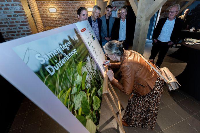 Burgemeester Annemieke van de Ven van Reusel-De Mierden zet haar handtekening onder de afspraak om voor 2026 de opmars van de Japanse duizendknoop te stuiten.