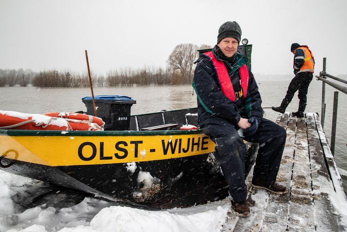 Schipper John Maatman is stevig ingepakt tegen de kou. Sinds vandaag vaart hij op het puntje naar Fortmond. De buurtschap is onbereikbaar voor auto's door het hoge water van de IJssel en het koude weer.