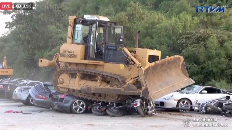 Een bulldozer van de Filipijnse douane verplettert Lamborghini's en Porsches. Beeld rv