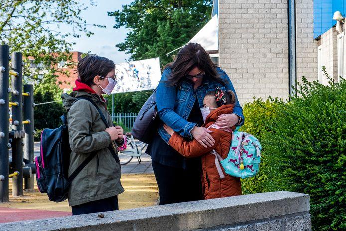 Daphne van Zwam uit Tiel knuffelt haar dochters voordat ze weer naar school gaan. Aimée en Britt  wilden zelf graag een mondkapje op.