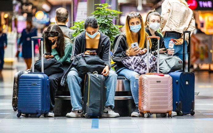 Drukte in de vertrekhallen van Schiphol met mensen die deze zomervakantie op reis gaan naar het buitenland.