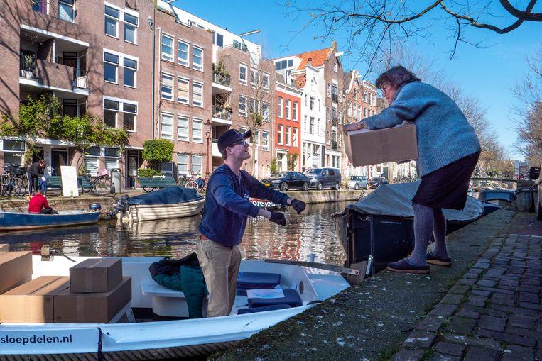 Een Amsterdammer neemt een bestelde boodschappenbox van SupportYourLocals aan.  Beeld Mariette Carstens / HH