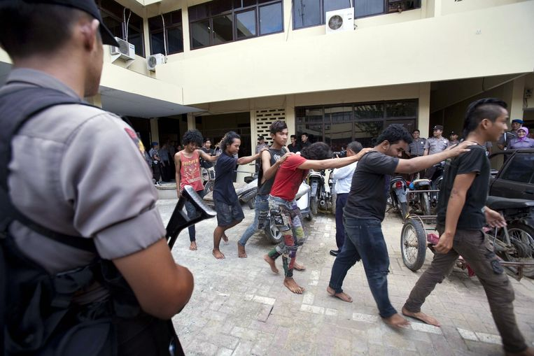 In this photograph taken on December 13, 2011 police escort a group of arrested Indonesian punks in Bandah Aceh police station in Aceh province. Sharia police are