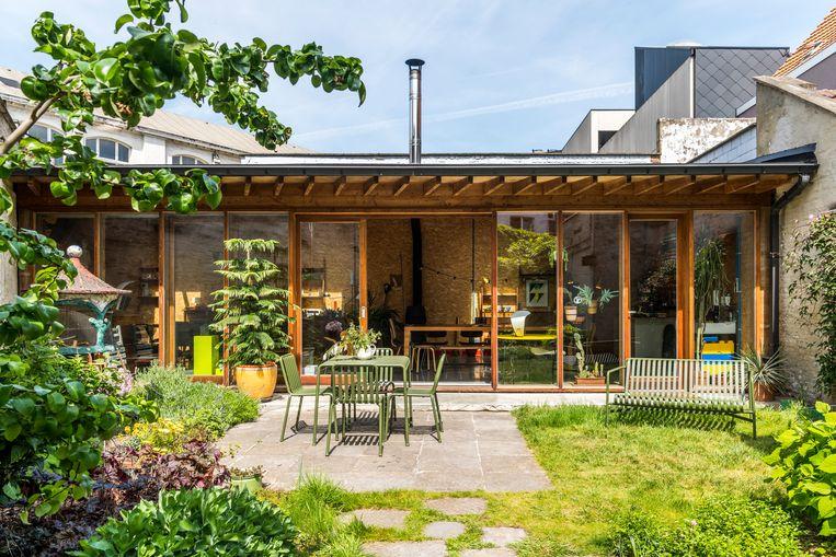 In de tuin staat het atelier met glazen gevel die bijna volledig open kan. De tuinset is van Hay. Het terras legden Sara en Pieter zelf aan met stenen uit De Bijloke die Sara's papa nog had liggen. Het kitscherige betonnen vogelhuis is ook een cadeau van haar vader. Beeld Luc Roymans