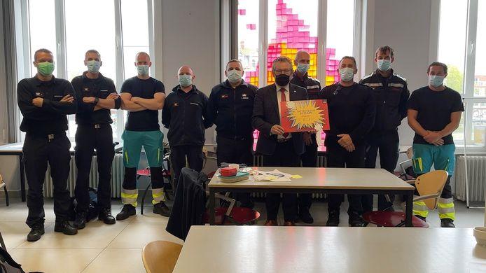 Burgemeester Dirk De fauw bedankte de brandweermannen voor hun inzet en had een cadeau bij.