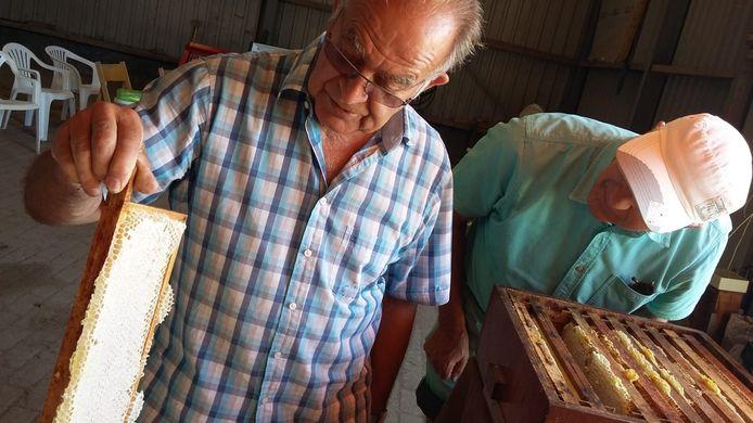 Wim Bil laat een raat zien aan Cees van de Sluis, bezoeker van de open Imkerijdag