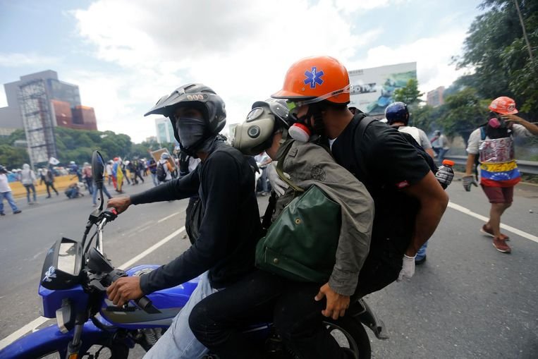 Een door traangas verdoofde demonstrant wordt afgevoerd. Beeld ap