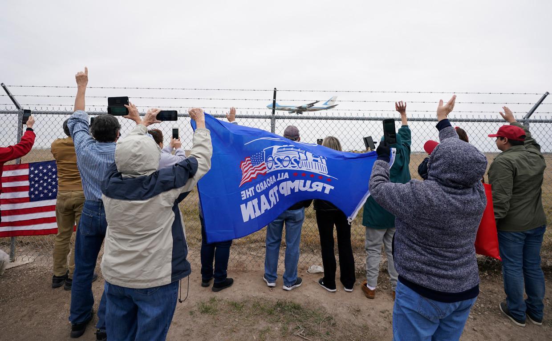 Aanhangers verwelkomen het vliegtuig van president Donald Trump op de luchthaven van het Texaanse Harlingen, waar hij gisteren arriveerde om een bezoek te brengen aan een stuk grenshek. Beeld AP