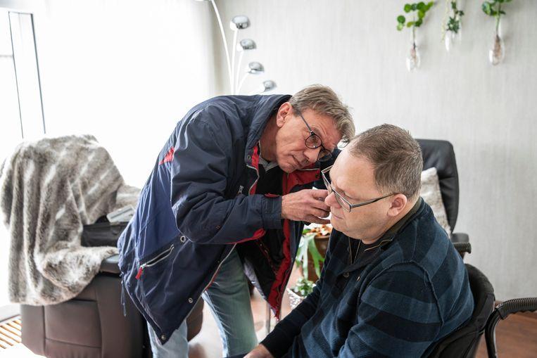 Huisarts Geert Smit in zijn praktijk en bij een patiënt.  Beeld null