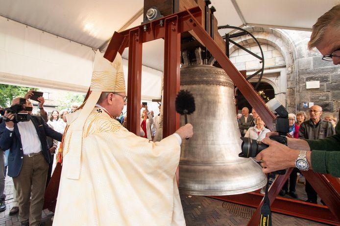 Kardinaal Eijk besprenkelt de nieuwe besklok van het carillon met wijwater.