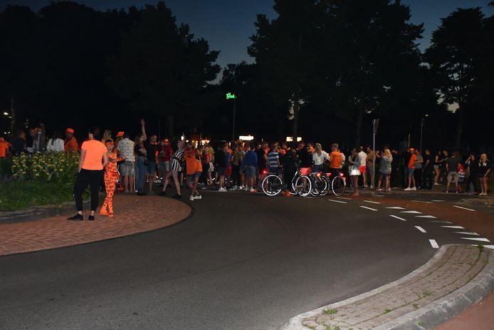 Een groep supporters viert feest op de rotonde in Vroomshoop na de zege van Oranje (3-2) op het EK.