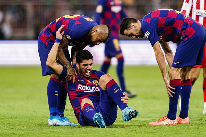 Luis Suárez kermt van de pijn nadat hij donderdag zijn meniscusblessure opliep in Jeddah, Saudi-Arabië.