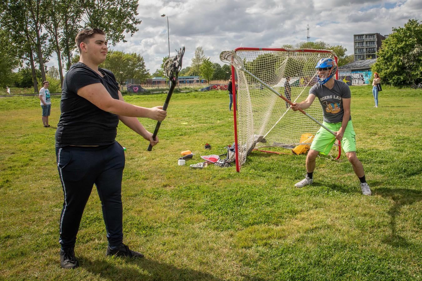Daniël Sterenborg (r) leert Loek Jansen de beginselen van lacrosse
