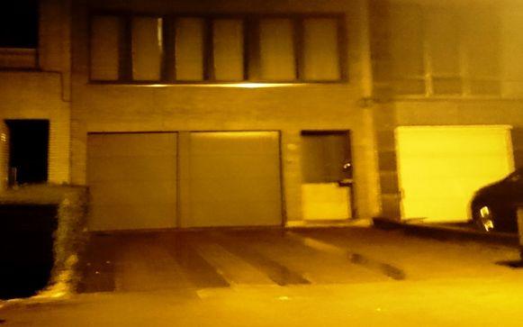 Het gebouw in de Deken de Winterstraat in Berchem, waar zaterdagochtend een springtuig tegen gegooid werd. Er staat een houten plaat voor de beschadigde voordeur.