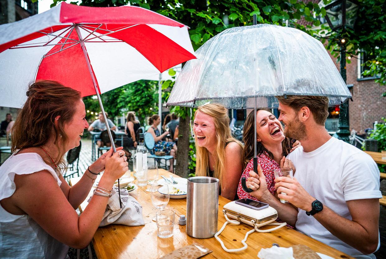 Plezier onder de paraplu op een heropend terras in Leiden, juni vorig jaar.  Beeld  Freek van den Bergh / de Volkskrant