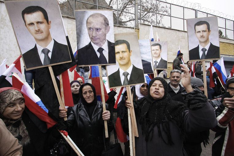 Demonstranten dragen portretten van Assad en Poetin mee tijdens een demonstratie van regeringsaanhangers in Damascus eerder dit jaar. Beeld ap