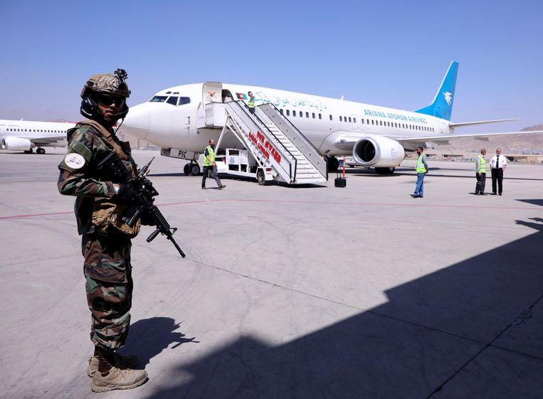 Een Taliban houdt de wacht bij een vliegtuig dat vanuit de Afghaanse provincie Kandahar is aangekomen op het vliegveld van Kaboel. Beeld REUTERS