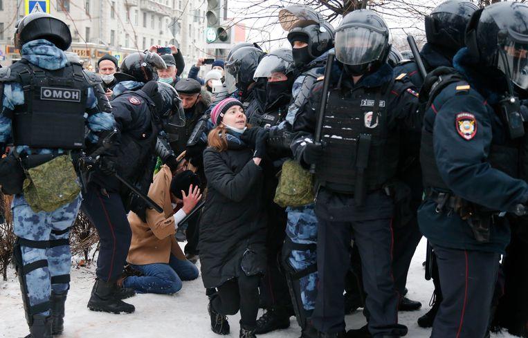 De politie houdt een man vast terwijl een andere politieagent een jonge vrouw in het midden tegenhoudt tijdens een protest tegen de gevangenneming van oppositieleider Alexei Navalny in Moskou, Rusland Beeld AP