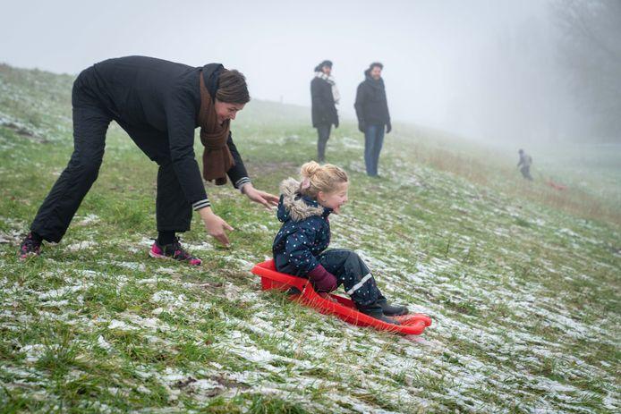 Sleeën in Huissen. 'Ik zag kinderen vol verwachting met een sleetje op de dijkhelling vast oefenen in het modderige gras.'