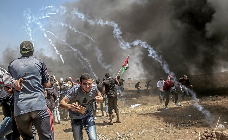 Palestijnse demonstranten zoeken dekking omdat het Israëlische leger traangas afvuurt. Beeld EPA