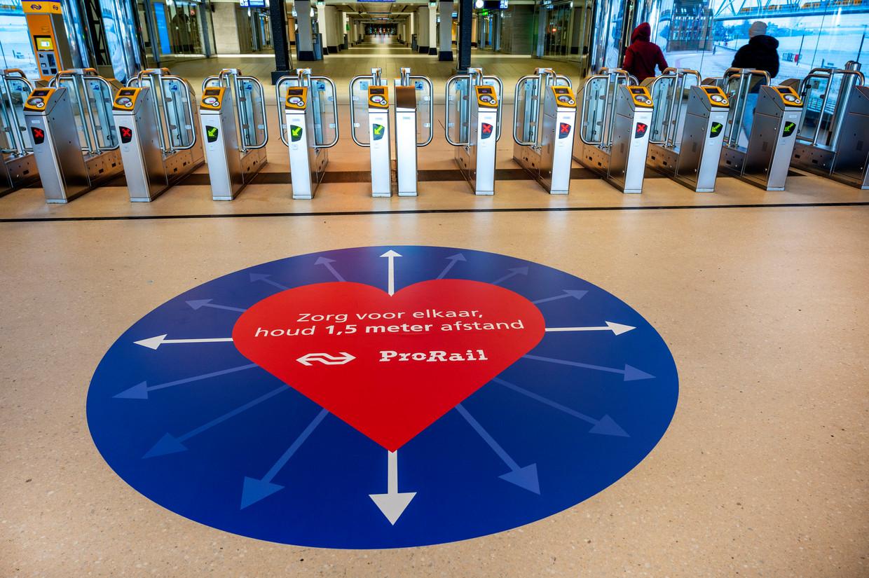 Zondag en maandag worden op diverse middelgrote en grote stations vloerstickers geplakt, bijvoorbeeld op Amsterdam Centraal. Beeld ANP