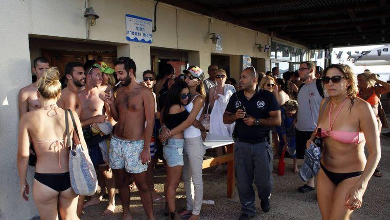 Strandgangers in Tel Aviv zoeken een schuilplaats bij het waarschuwingssignaal van de sirenes. Beeld null