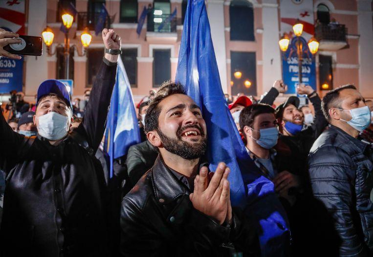 Aanhangers van regeringspartij Georgische Droom vieren de voorlopige uitslag van de verkiezingen in de Georgische hoofdstad Tbilisi. Beeld EPA
