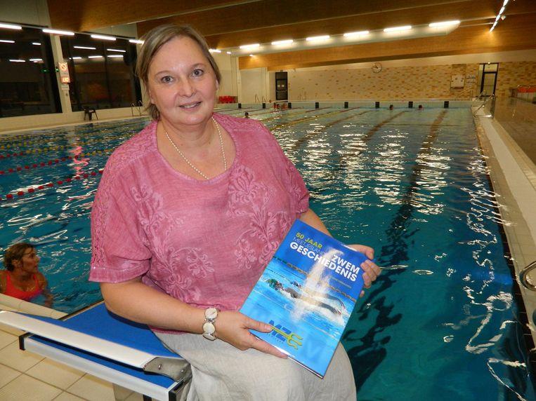 Carine Verbauwen met haar boek in het nieuwe zwembad van Eeklo.