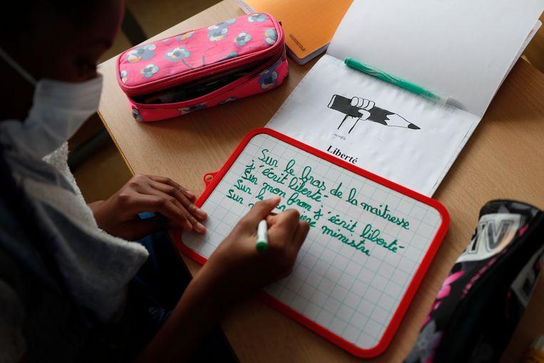 Het meisje is een van de schoolkinderen in Straatsburg die les krijgen in de regels voor vrijheid van meningsuiting en scheiding van kerk en staat.  Beeld AP