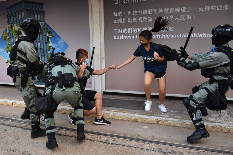 De politie vandaag in gevecht met een stel dat gezichtsmaskertjes draag in het Central district van Hongkong.
