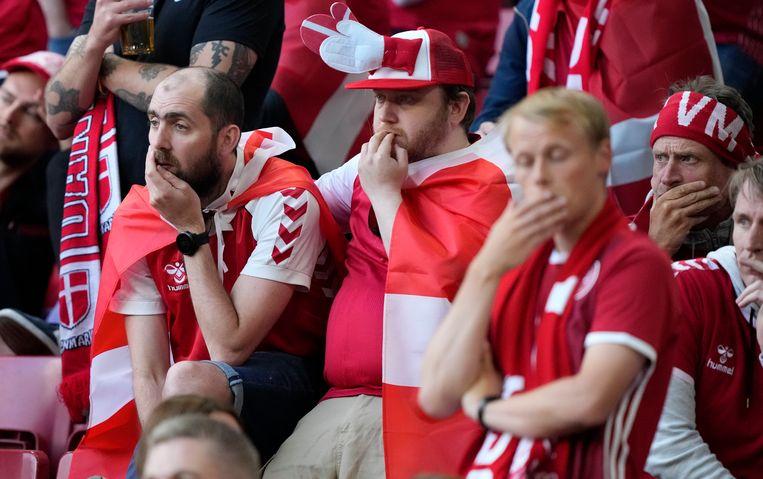 Deense fans reageren geschokt als  Christian Eriksen op het veld ineenzakt. Beeld AP