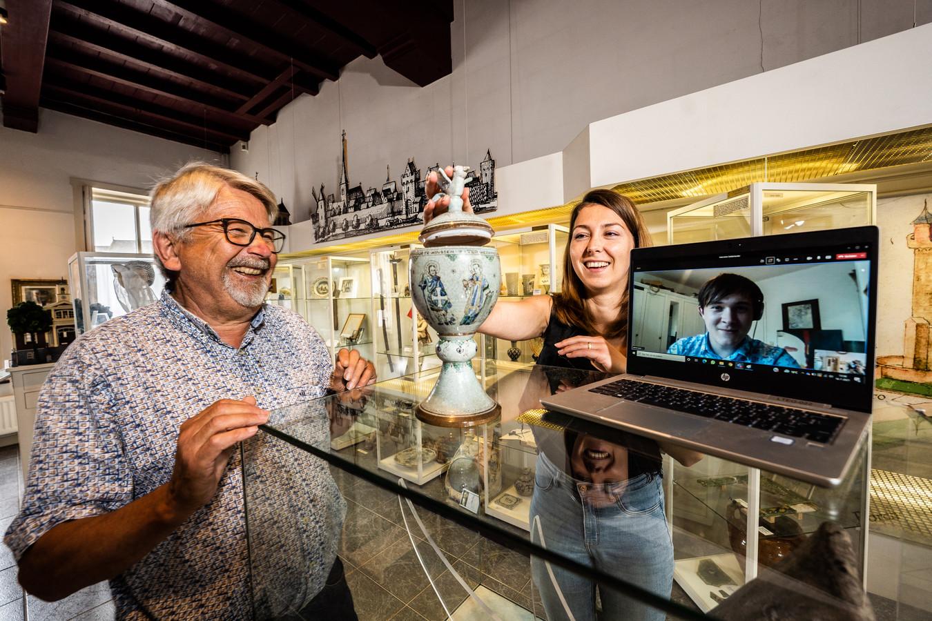 Koos Meeuwsen en Lian van der Zon bekijken samen een object in het stadsmuseum in Huissen. Via de laptop praat Jelle Hofs vanuit het Duitse Oldenburg mee.