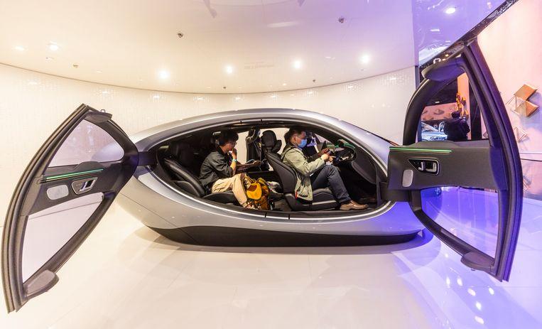 Bezoekers van de Auto Shanghai-motorshow proberen een nieuwe conceptauto van Mercedes uit.  Beeld EPA