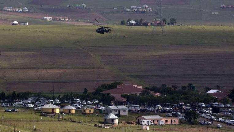 Een legerhelikopter vliegt zaterdag boven Qunu terwijl de rouwstoet met het lichaam van Mandela in het dorp arriveert. Beeld reuters
