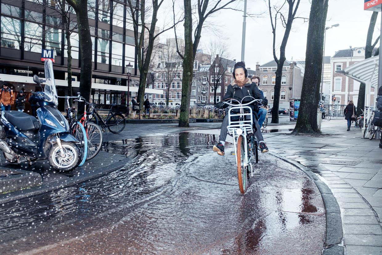 Door de innovatieve projecten om het regenwater op te slaan, zou een tafereel als dit uit het Amsterdamse straatbeeld moeten verdwijnen.  Beeld Jakob van Vliet