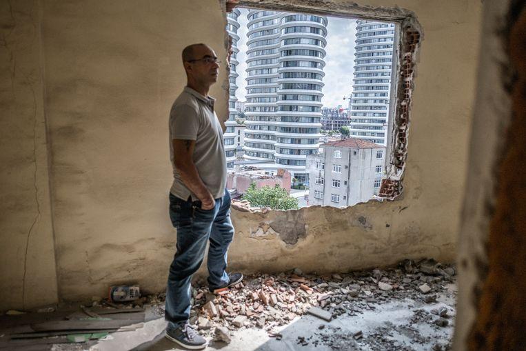 Engin Akguzel in een verlaten en vervallen huis in Fikirtepe, met zicht op de nieuwbouw. Beeld Joris Van Gennip