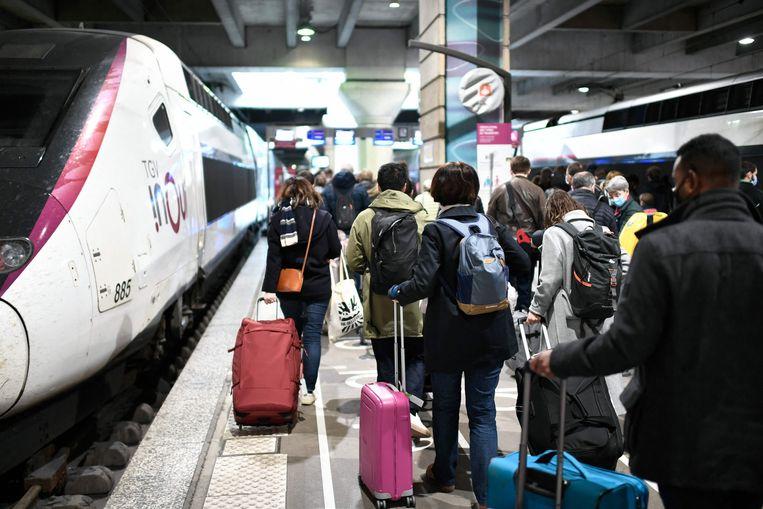 Passagiers lopen naar hun trein op het Montparnasse-station in Parijs. Beeld AFP