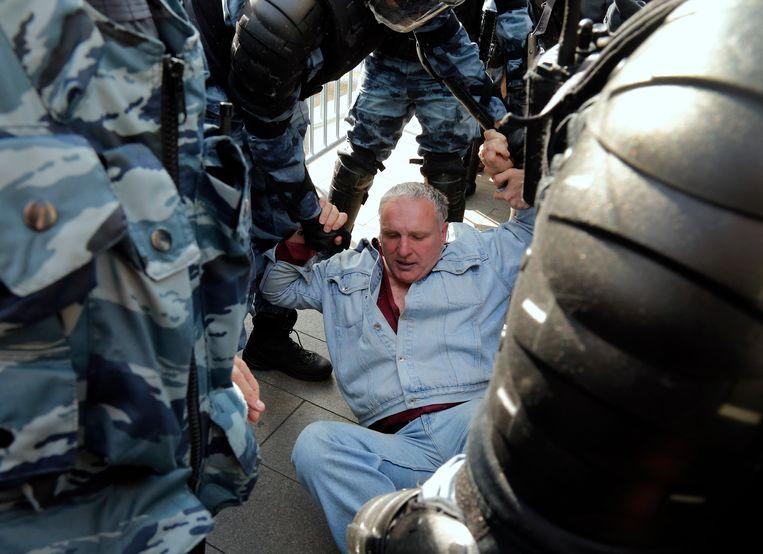 Een demonstrant in Moskou wordt door de politie opgepakt. Beeld AP