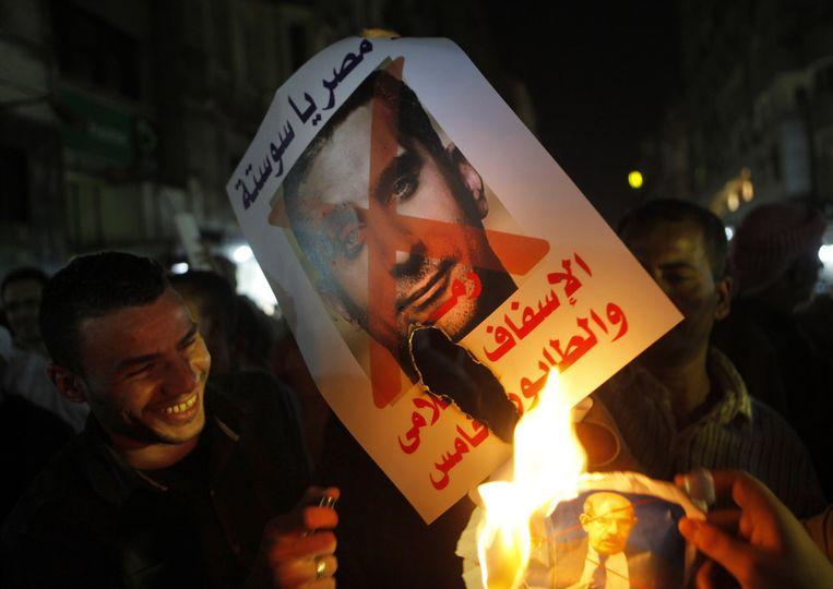 Aanhangers van de huidige machthebbers verbranden een foto van de satiricus Bassem Youssef . Beeld AP