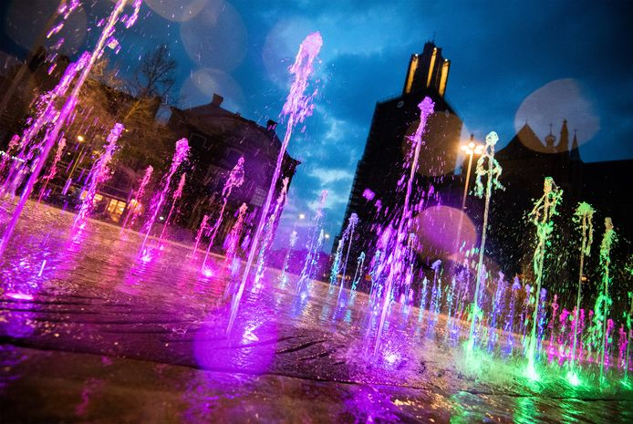 De fontein van de Markt in Arnhem, pal voor het Gelderse provinciehuis, in regenboogkleuren.