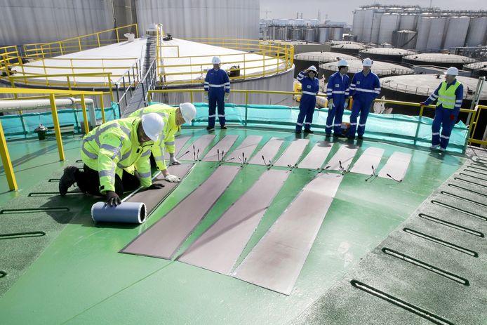 Zafar Idu en Joost Horstink (in gele jassen) brengen het zonnefolie aan op een olieopslagtank.