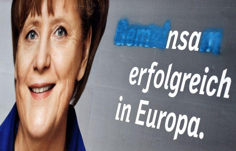 Een verkiezingsposter met Angela Merkel uit 2014, met de tekst 'Samen succesvol in Europa'. Het woord 'gemeinsam' (samen) is half uitgeveegd waardoor enkel de letters 'nsa' overblijven. Beeld AFP