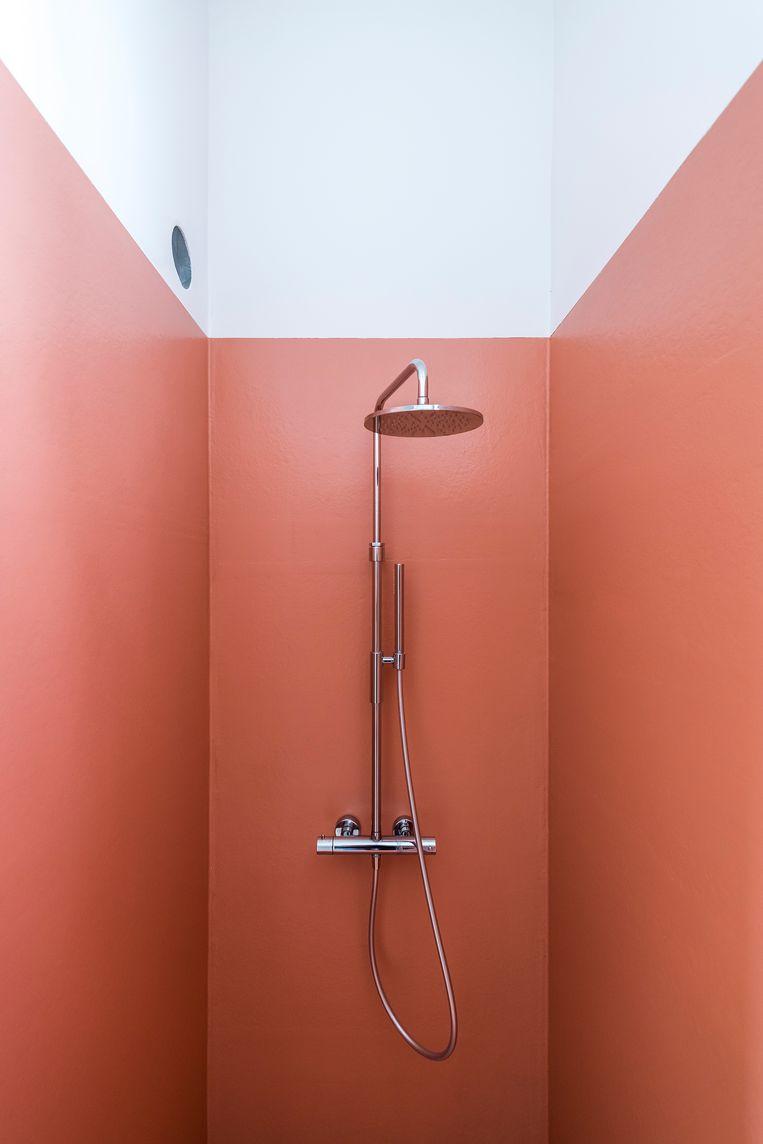 Virginia en Amaury zijn uiteindelijk ook gezwicht voor een shot kleur in de badkamer. In de koraalrode douche is het vrolijk wakker worden.   Beeld